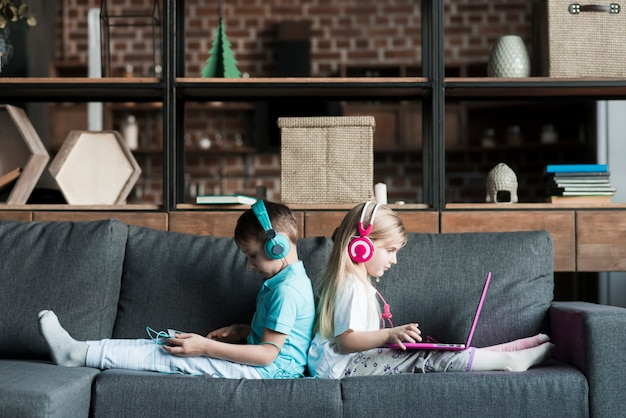 Two kids on couch with laptop Free Photo
