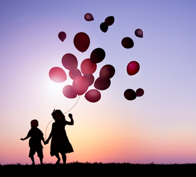 Two kids outdoor holding balloons together Free Photo