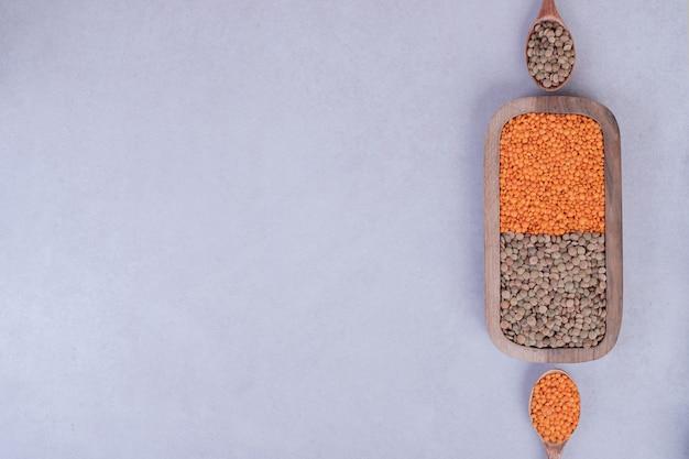 スプーンで木の板に生豆とレンズ豆の2種類。 無料写真
