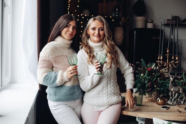 快適な冬服を着た2人の女性が、派手な眼鏡をかけ、互いに近くに立っています。 無料写真