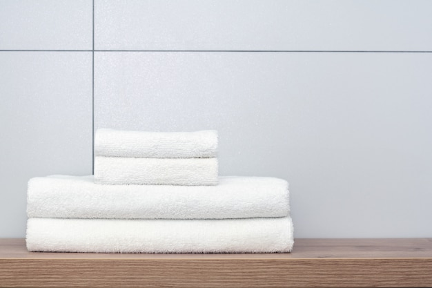 Two large and two small neatly folded white towels lie on a wooden shelf against the background of ceramic tiles. Premium Photo