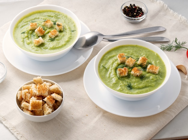 Two large white bowl with vegetable green cream soup of broccoli, zucchini Premium Photo