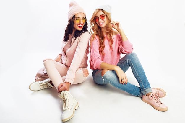 2人の笑っている女の子、白い背景の上のスタジオでポーズをとる親友。トレンディなピンクの冬服。 無料写真