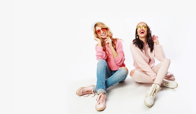 두 웃는 여자, 흰색 배경에 스튜디오에서 포즈 가장 친한 친구. 유행 분홍색 겨울 복장. 무료 사진