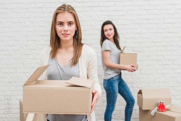 Two lesbian women holding cardboard boxes in hand standing near the white brick wall Free Photo
