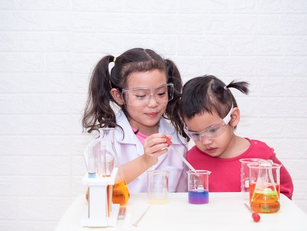 Two little asian cute girl role playing a scientist with equipment on white table. Premium Photo