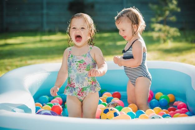 Le due bambine che giocano con i giocattoli in piscina gonfiabile nella giornata di sole estivo Foto Gratuite