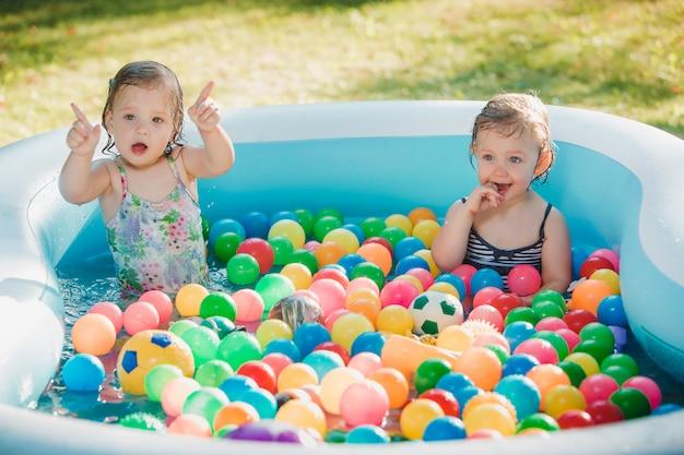 Le due bambine che giocano con i giocattoli in piscina gonfiabile in giornata di sole estivo Foto Gratuite