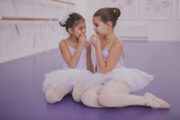Two little ballerinas talking after dancing lesson Premium Photo