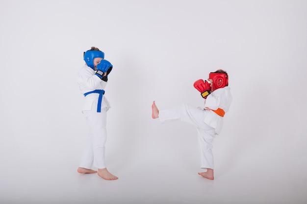 Two little boy in a white kimono, helmet, gloves compete on a white wall Premium Photo