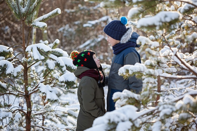 Two little boys friends hug each other in snowy winter day. brother love. concept friendship. Premium Photo