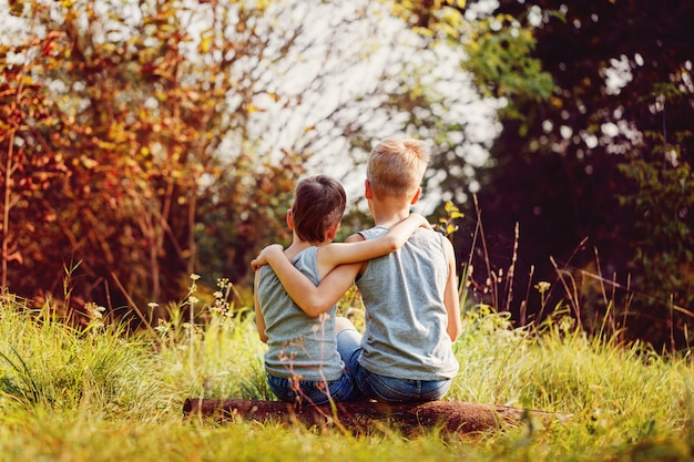 Two little boys friends hug each other in summer sunny day. Premium Photo