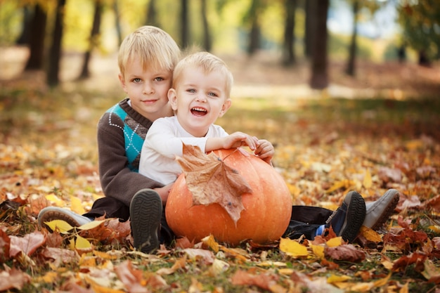 Two little brothers sitting on grass and embracing with huge pumpkin in autumn day Premium Photo
