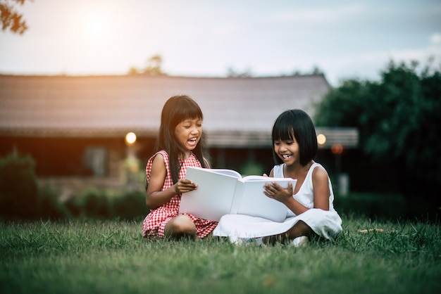 Two little girl friends in the park on the grass reading a book and learn Free Photo