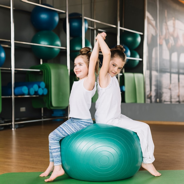 Two little girl sitting back to back on exercising ball together Free Photo