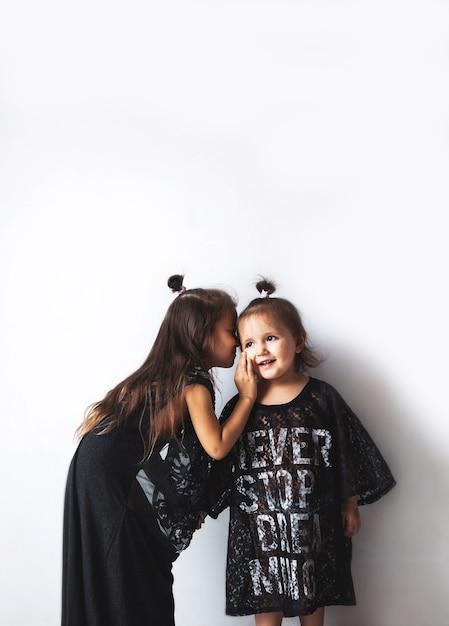 Две маленькие девочки болтают, изолированные на белом, девочки, одетые в маминую одежду Premium Фотографии