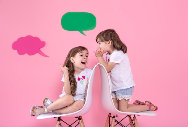 Two little girls on colored wall with speech icons Free Photo