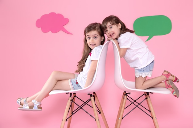 Two little girls on colored with speech icons Free Photo