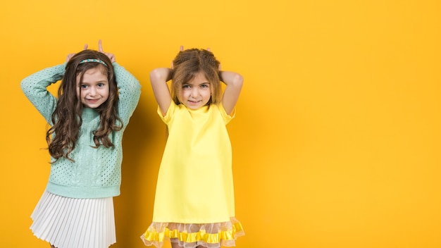 Two little girls making horns with fingers Free Photo