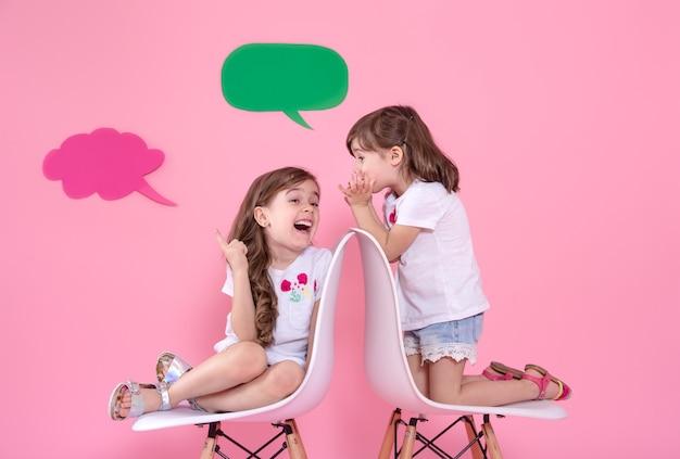 スピーチアイコンと色の壁に2人の少女 無料写真