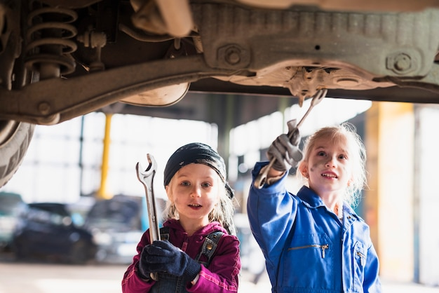 Two little girls in overalls repairing car with spanners Free Photo