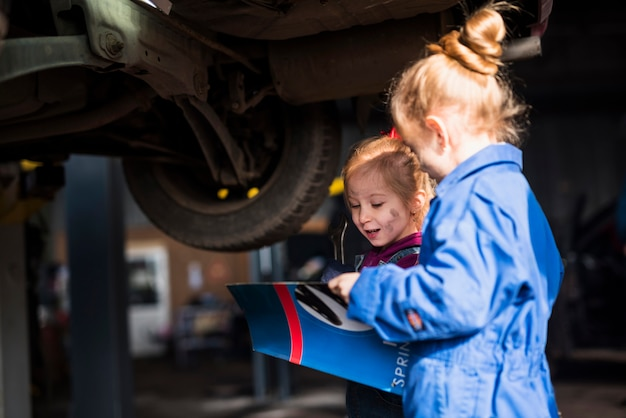 Two little girls in overalls with spanner reading magazine Free Photo