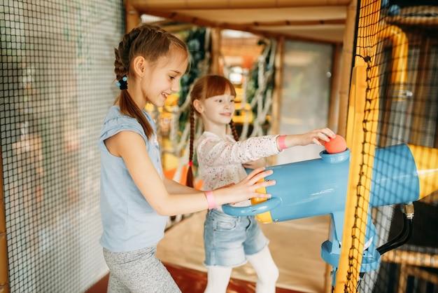 2人の少女がゲームセンターでエアガンを果たしています。 Premium写真