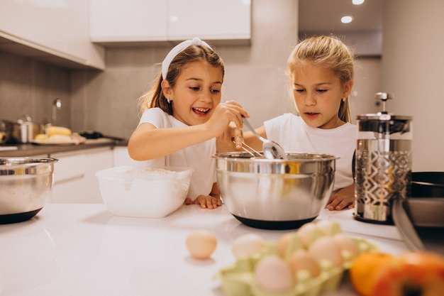 Two little girls sisters cooking at kitchen Free Photo