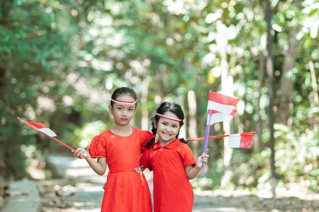 Две маленькие девочки, стоящие в красной рубашке и красно-белом атрибуте, держат красно-белые флаги Premium Фотографии