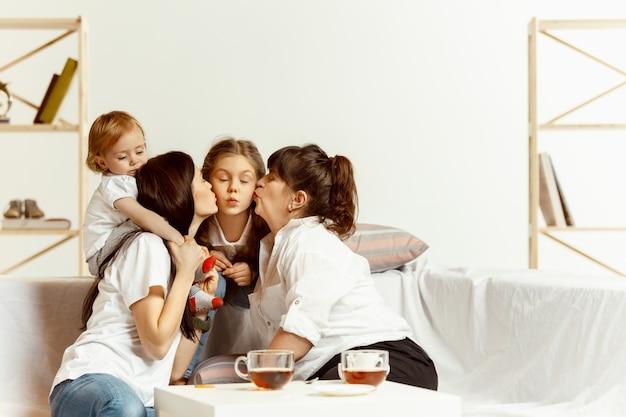 Две маленькие девочки, их привлекательная молодая мать и их очаровательная бабушка, сидят на диване и проводят время вместе дома. поколение женщин. международный женский день. с днем матери. Бесплатные Фотографии