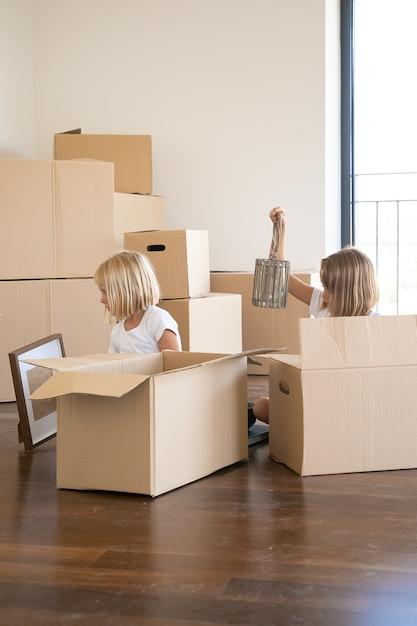 Due bambine che disimballano le cose nel nuovo appartamento, sedendosi sul pavimento e prendendo oggetti da scatole di cartone aperte Foto Gratuite