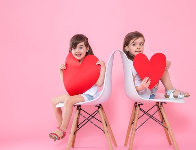 컬러 벽에 마음을 가진 두 어린 소녀 무료 사진