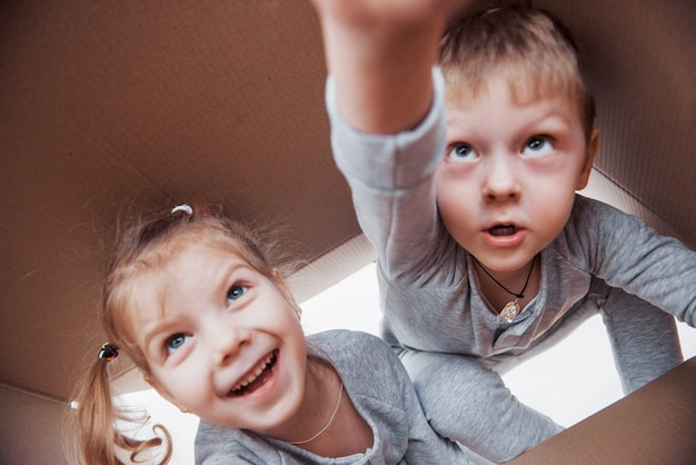 Two a little kids boy and girl opening a cardboard box and climbing in the middle of it. children have fun Premium Photo