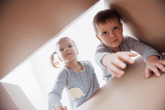 Two a little kids boy and girl opening cardboard box and looking inside with surprise Premium Photo