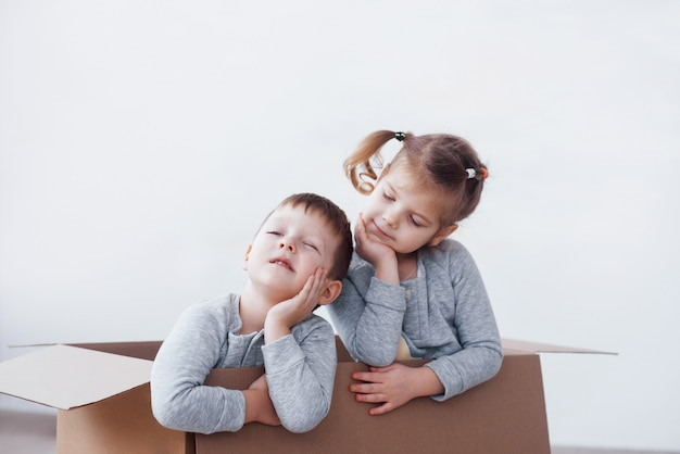 Two a little kids boy and girl playing in cardboard boxes. concept photo. children have fun Premium Photo