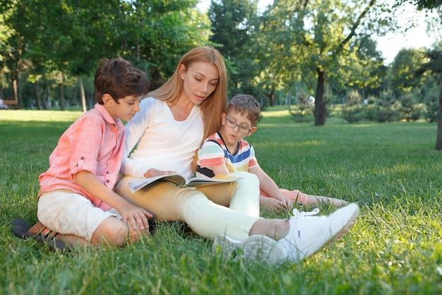 公園の屋外で女教師と本を読んでいる2人の小さな男子生徒 Premium写真