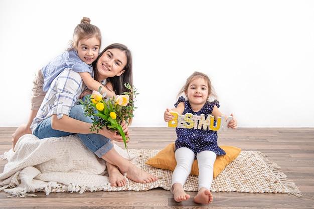 Две сестренки поздравляют маму с днем матери. Бесплатные Фотографии