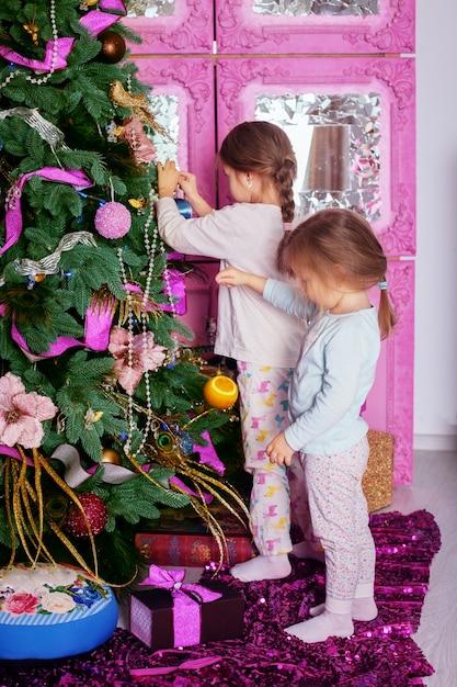 Две маленькие сестры в пижаме украшали елку. Premium Фотографии