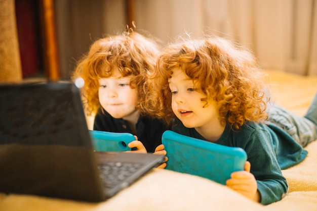 Two little twin sisters holding digital tablet lying on bed looking at laptop Free Photo