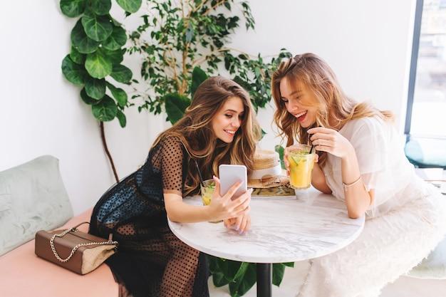 モダンなインテリアと笑いのカフェで休んでいる2人の長髪の女の子 無料写真
