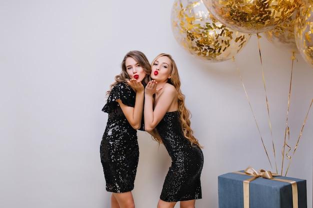 생일 파티에서 키스 얼굴 표정으로 포즈를 취하는 비슷한 검은 드레스에 두 사랑스러운 여자. 풍선 및 선물 옆에 서서 공기 키스를 보내는 장발 유럽 아가씨. 무료 사진