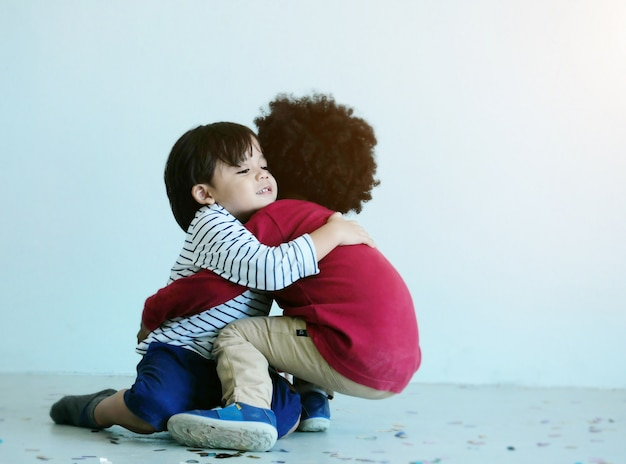Two lovely little boy play and hugging together in school. Premium Photo