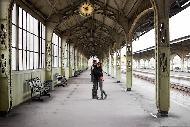 Two lovers hug and kiss on the railway station Free Photo