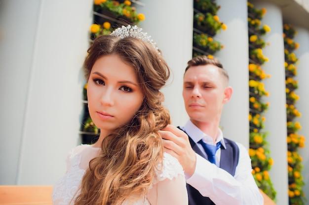 2人の恋人がベンチに座って、結婚式の写真撮影中に新婚夫婦が互いに腕を組んで休む、白いドレスを着た花嫁と美しいスーツを着た新郎が公園で引退しました。 Premium写真