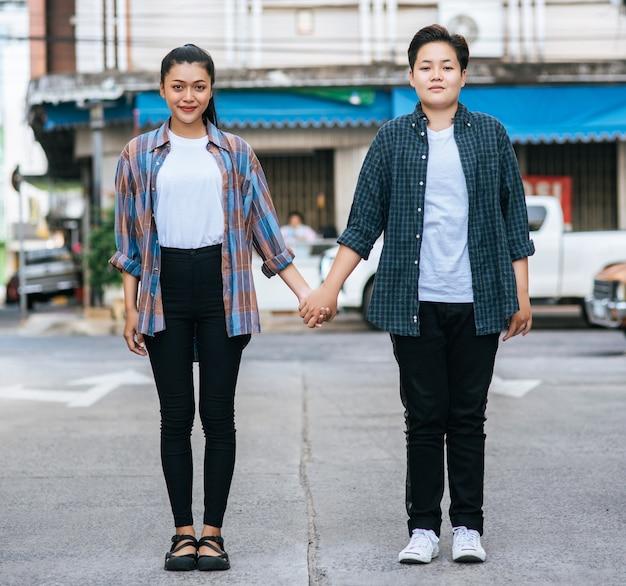 Due donne amorevoli in piedi e mano nella mano sulla strada. Foto Gratuite