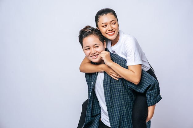 Due donne amorevoli indossavano camicie a righe e cavalcavano la schiena. Foto Gratuite