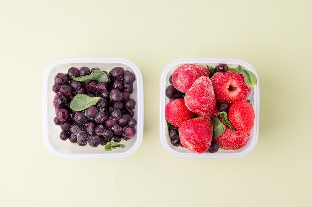 黒いスペースに冷凍イチゴとスグリが入った2つのランチボックス。 Premium写真