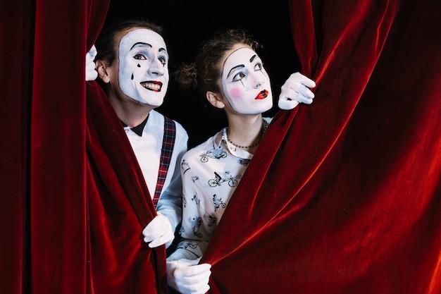 赤いカーテンを見ている2人の男性と女性のmimeアーティスト Premium写真