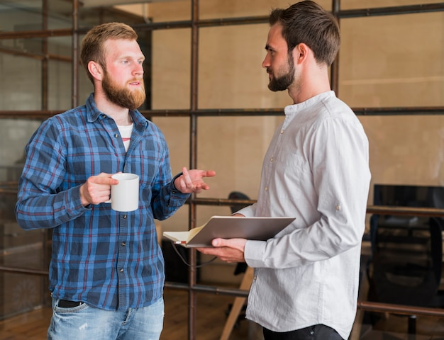 Two male colleague discussing with each other at workplace Free Photo