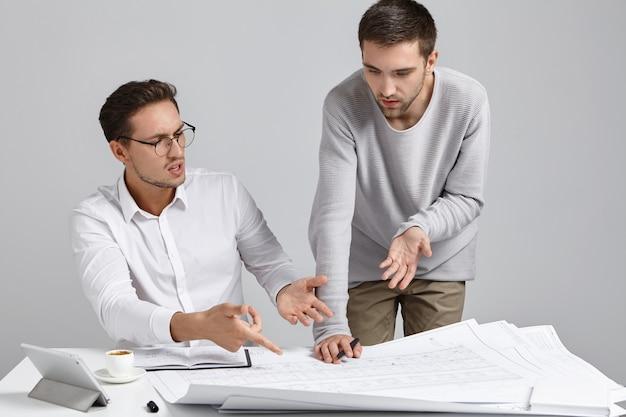 두 남자 동료 건축가가 건축 계획에 대해 논쟁을 벌이며 자신의 관점을 표현 무료 사진